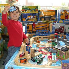 child in red shirt playing with trainset